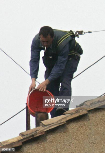An employee works on the chimney on the roof of the Sistine Chapel at the Vatican, 12 April 2005. Cardinals will be electing the 265th pope next week...