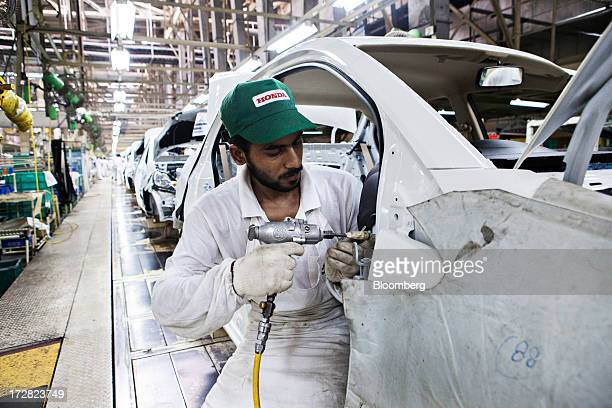 An employee works on the dashboard of a Honda Motor Co Amaze vehicle on the production line of the Honda Cars India Ltd plant in Greater Noida India...