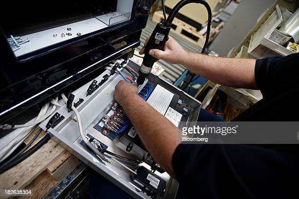 An employee works on the electrics for an AGA 3oven Total Control range cooker produced by AGA Rangemaster Plc during the manufacturing process at...
