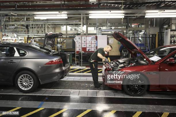 An employee works on the engine bay of a Jaguar automobile as it moves through the production line at Tata Motors Ltd's Jaguar assembly plant in...