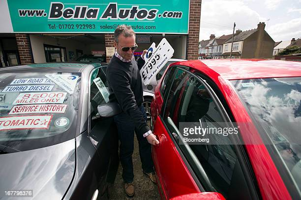 An employee works on the forecourt of an independent secondhand car dealership in LeighonSea UK on Monday April 29 2013 European car sales are...