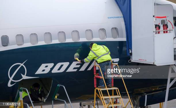 An employee works on the fuselage of a Boeing 737 MAX 9 test plane outside the company's factory on March 14 2019 in Renton Washington The 737 MAX...