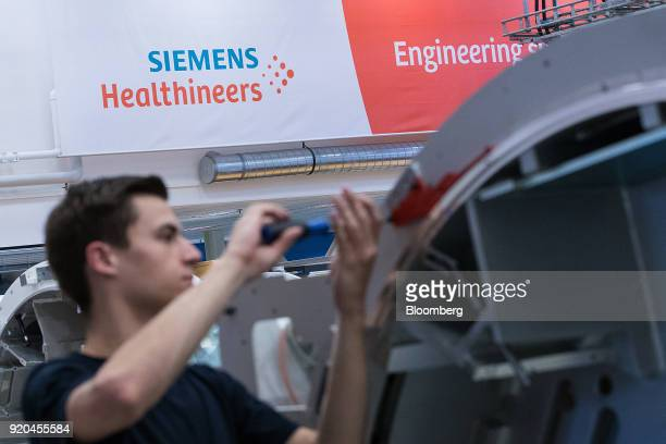 An employee works on the gantry of a Siemens Somatom computerized tomography scanner machine on the assembly line at the Siemens AG Healthineers...