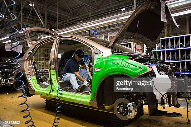An employee works on the interior assembly of an automobile on the production line at Hyundai Motor Co.'s plant in Nosovice, Czech Republic, on...