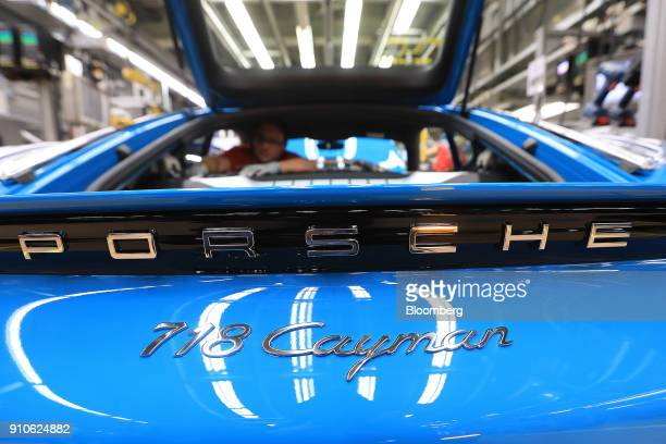An employee works on the interior of a Porsche 718 Cayman luxury automobile on the production line inside the Porsche AG factory in Stuttgart Germany...