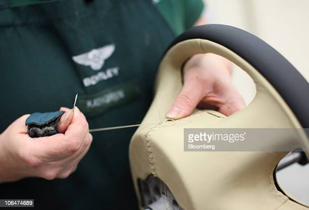 An employee works on the leather steering wheel for a Bentley Mulsanne automobile at the Volkswagen AG Bentley factory in Crewe UK on Tuesday Nov 2...