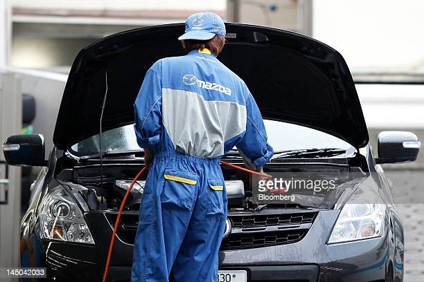 An employee works on the maintenance of a Mazda Motor Corp vehicle at a dealership in Tokyo Japan on Wednesday May 23 2012 Fiat SpA agreed to jointly...