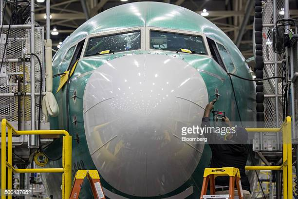 An employee works on the nose of a Boeing Co 737 MAX airplane on the production line at the company's manufacturing facility in Renton Washington US...