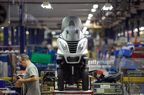 An employee works on the production line of the Peugeot Metropolis motorcycle series by French car and motorcycle maker PSA Peugeot Citroen on...