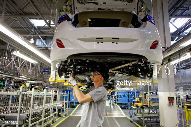 An employee works on the suspension assembly of a Hyundai Motor Co. Automobile inside the company's manufacturing plant in Nosovice, Czech Republic,...