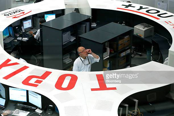 An employee works on the trading floor of the Tokyo Stock Exchange in Tokyo Japan on Thursday Oct 17 2013 Japanese shares rose with the Topix index...