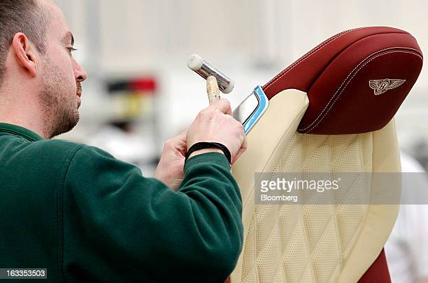 An employee works on the upholstery of a Bentley carseat on the production line at the Bentley Motors Ltd workshop in Crewe UK on Thursday March 7...