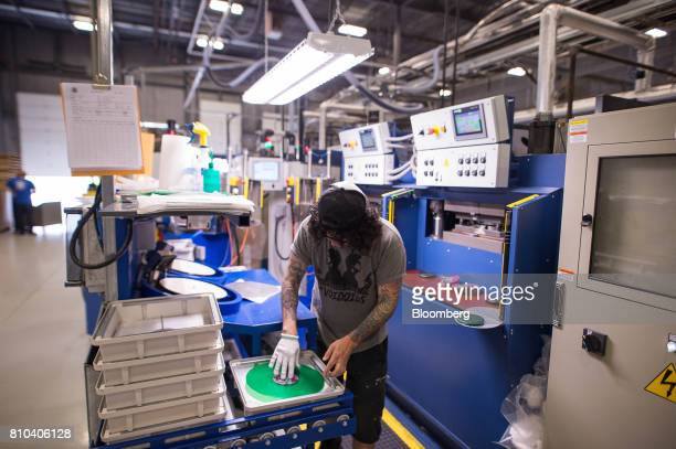 An employee works on the vinyl record pressing line at the Precision Record Pressing facility in Burlington Ontario Canada on Friday June 30 2017...