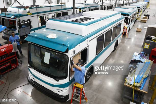 An employee works on the window frame of an electric bus at the BYD Coach and Bus factory in Lancaster California US on Thursday Oct 5 2017 BYD...