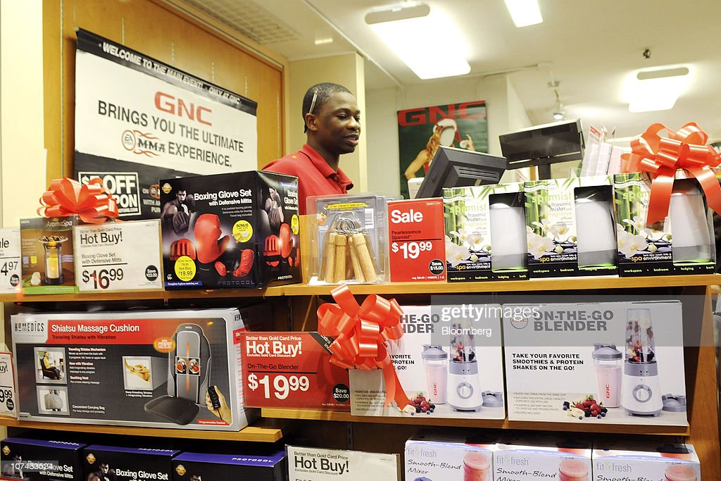 an employee works the cash register at a gnc store as seen