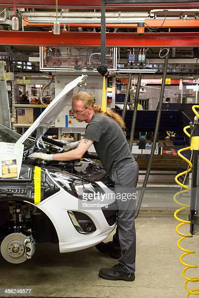 An employee works under the hood of an Opel Corsa automobile at the Adam Opel AG factory operated by General Motors Co in Eisenach Germany on...