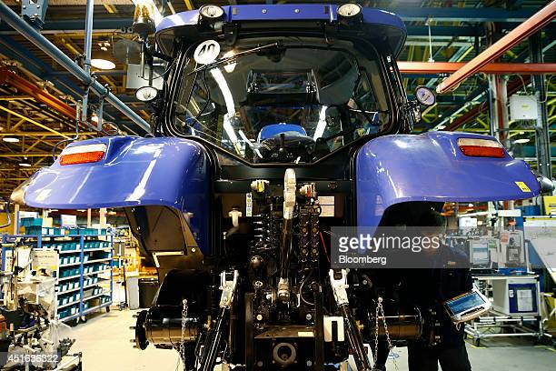 An employee works under the rear wheel arch of a New Holland tractor as it sits on the production line at CNH Industrial NV's assembly plant in...