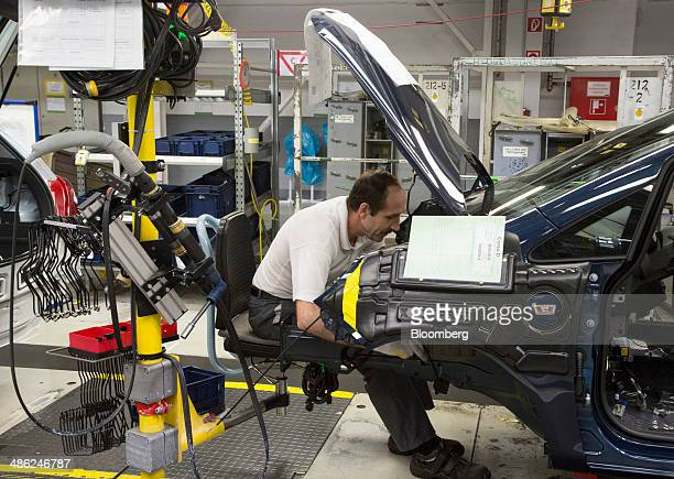 An employee works under the trunk of an Opel Corsa automobile at the Adam Opel AG factory operated by General Motors Co in Eisenach Germany on...