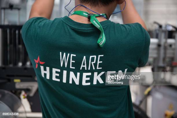 An employee works while wearing a tshirt that reads 'We Are Heineken' in the bottling plant at the Heineken NV brewery in Yangon Myanmar on June 15...