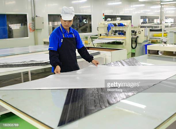 An employee works with carbon fiber sheets used in the manufacture of bicycles at the Giant Manufacturing Co Ltd factory in the Kunshan area of...