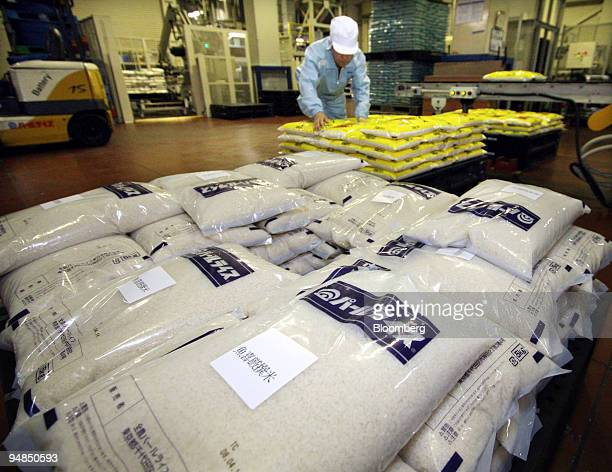 An employee works with sacks of rice at Zennoh Pearl Rice Corp's Chofu rice polishing plant in Tokyo Japan on Monday April 14 2008 As developing...
