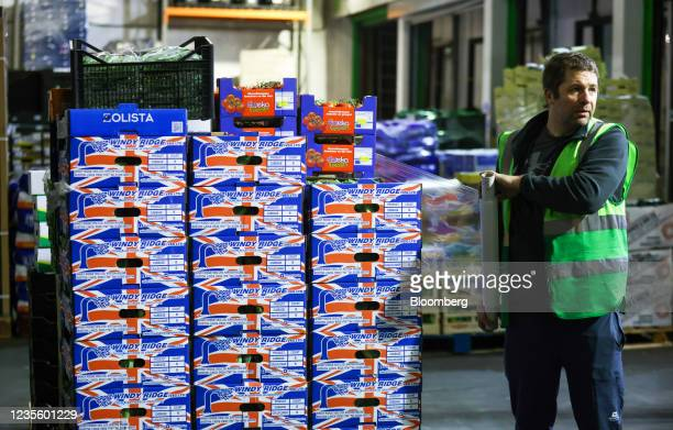 An employee wraps cellophane around a pallet of fresh British vegetables at New Covent Garden Market wholesale market in London, U.K., on Wednesday,...