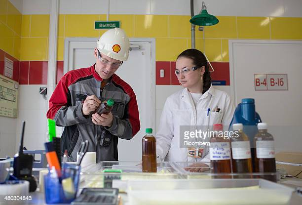An employee writes on an oil sample bottle as he stands with a technician in the control laboratory at Royal Dutch Shell Plc's lubricants blending...