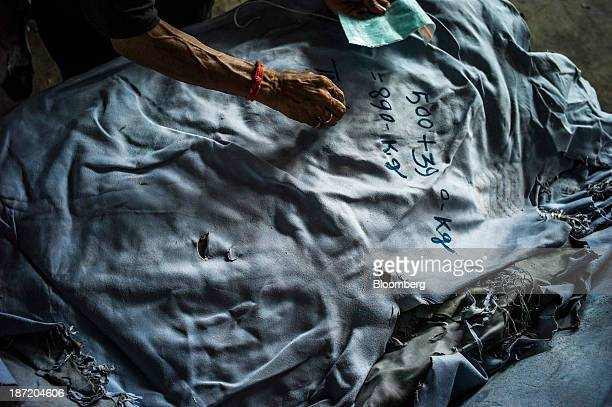 An employee writes product information onto the back of a tanned leather skin at the New Horizons Ltd tannery in the Bantala area of Kolkata West...