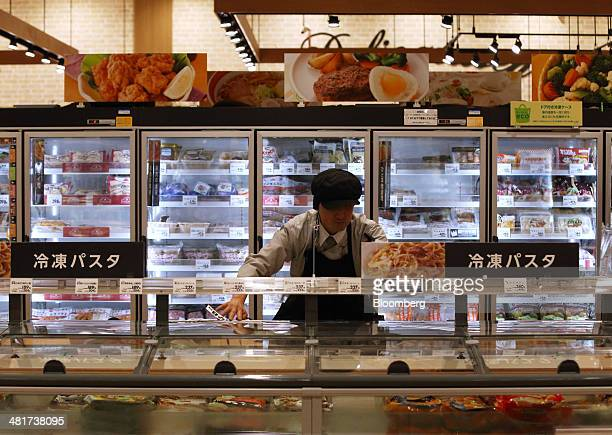An employees changes price signs on frozen foods ahead of a consumption tax hike at an Aeon Co supermarket in Chiba Japan on Monday March 31 2014 The...
