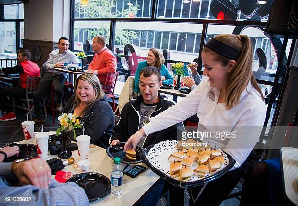 An employees gives chicken sandwich samples to guests during an event ahead of the grand opening for a ChickfilA restaurant in New York US on Friday...