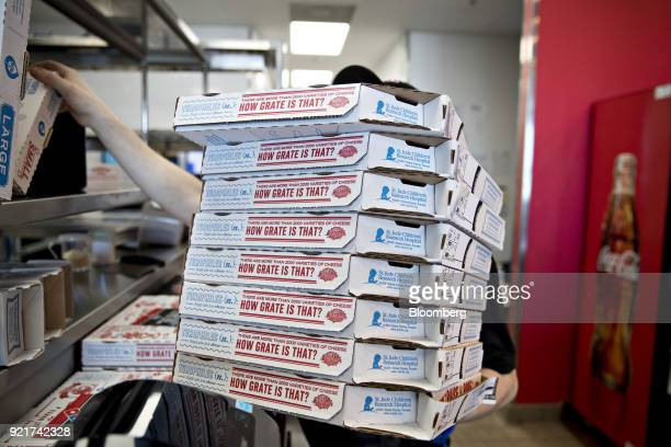 An employees holds pizza boxes at a Domino's Pizza Inc restaurant in Chantilly Virginia US on Tuesday Feb 20 2018 Domino's released earnings figures...