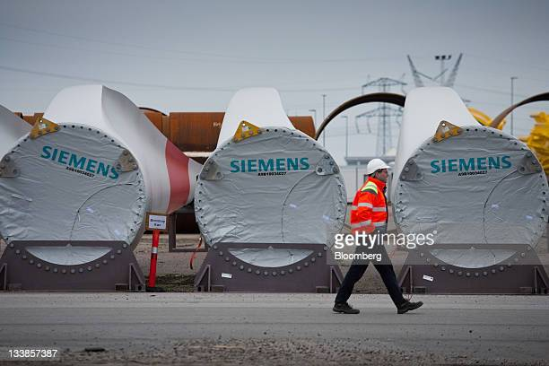 An employees passes finished wind turbine blades at the Siemens AG plant in Aalborg Denmark on Thursday Nov 10 2011 Siemens AG Europe's largest...