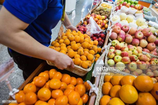 An employees places a basket of apricots in a fruit section at a Nomin Holding supermarket in Ulaanbaatar Mongolia on Saturday Aug 12 2017 The...
