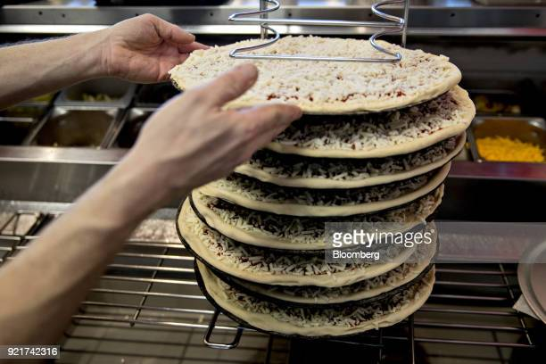 An employees places a pizza on a rack at a Domino's Pizza Inc restaurant in Chantilly Virginia US on Tuesday Feb 20 2018 Domino's released earnings...