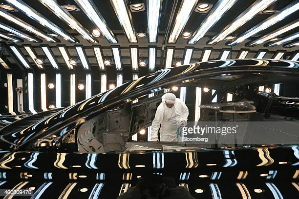 An employees polishes the bodywork of an Aston Martin Vantage automobile in the paintshop at Aston Martin Lagonda Ltd's manufacturing and assembly...