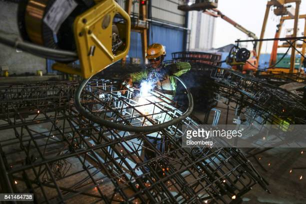 An employees welds the steel reinforcing frame of a precast concrete tunnel segment at the Mumbai Metro Rail Corp casting yard in Mumbai India on...