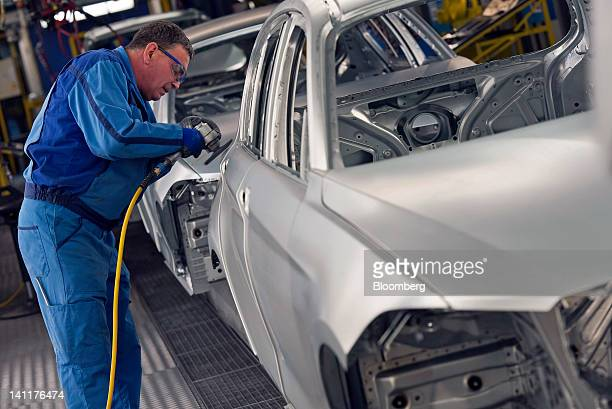 An employees works on the body shell of a Bayerische Motoren Werke AG 1series automobile as it travels along the production line at the company's...