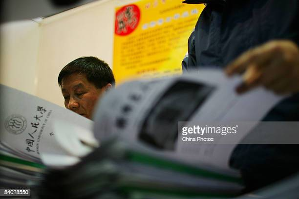 An employer checks hundreds of resumes at a job fair for postgraduate students on December 14 2008 in Beijing China Nearly 40000 applicants competed...