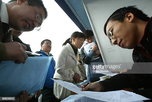 An employer views the information of a graduating university student at a job fair on November 26 2008 in Chengdu of Sichcuan Province China The...