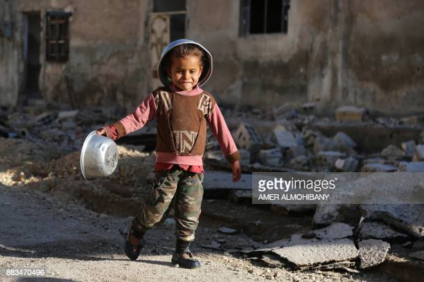 An empoverished Syrian boy walks with an empty bow on his head in the rebelheld town of alNashabiyah east of Damascus on November 30 2017 More than...