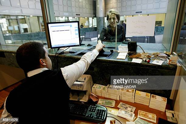 MOUSSAOUI An empployee serves a client at Lebanon's Central Bank in Beirut on November 24 2008 Lebanon for now has managed to steer clear of the...