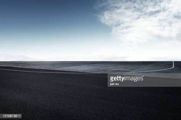 an empty airport runway under a blue sky - airfield stock pictures, royalty-free photos & images