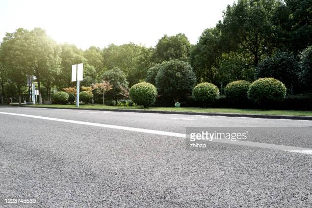an empty asphalt road beside the woods - close to stock pictures, royalty-free photos & images