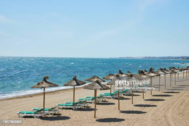 an empty beach in marbella, spain - spain stock pictures, royalty-free photos & images