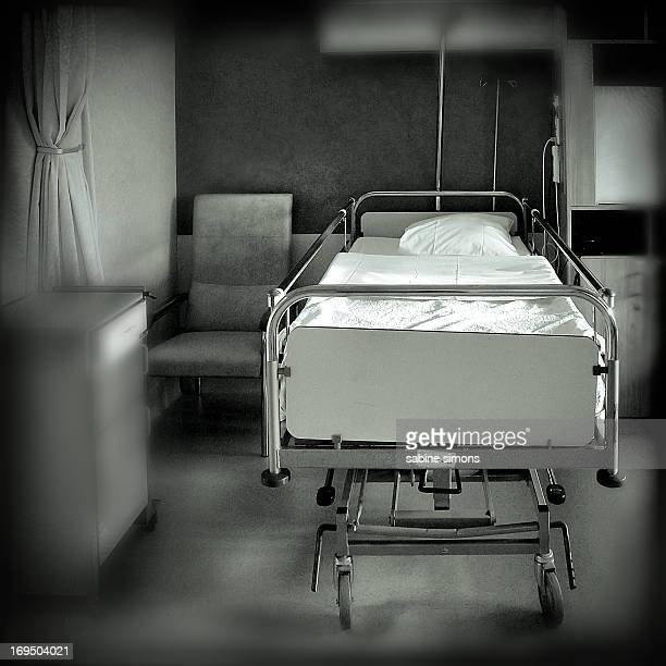 CONTENT] An empty bed in an old looking hospital Retro black and white hospital bed on wheels old fashioned