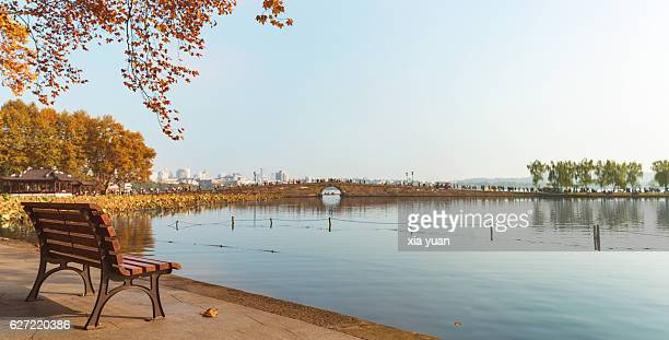 an empty bench  by lake in autumn,hangzhou,china - west lake hangzhou stock pictures, royalty-free photos & images