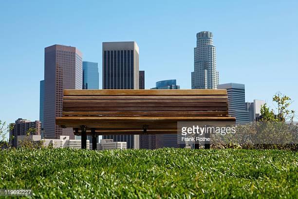 an empty bench in front of city skyline - banco asiento fotografías e imágenes de stock