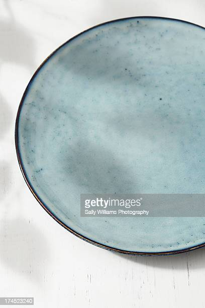 An empty blue plate on a white background