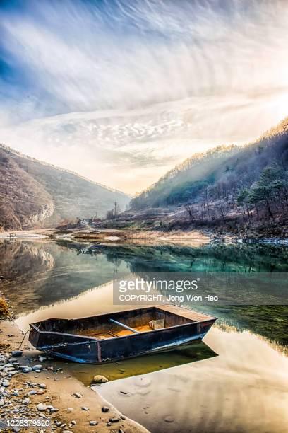 an empty boat on the river between mountains - pyeongchang stockfoto's en -beelden