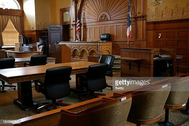 an empty, brown-paneled courtroom with flags - courtroom stock pictures, royalty-free photos & images